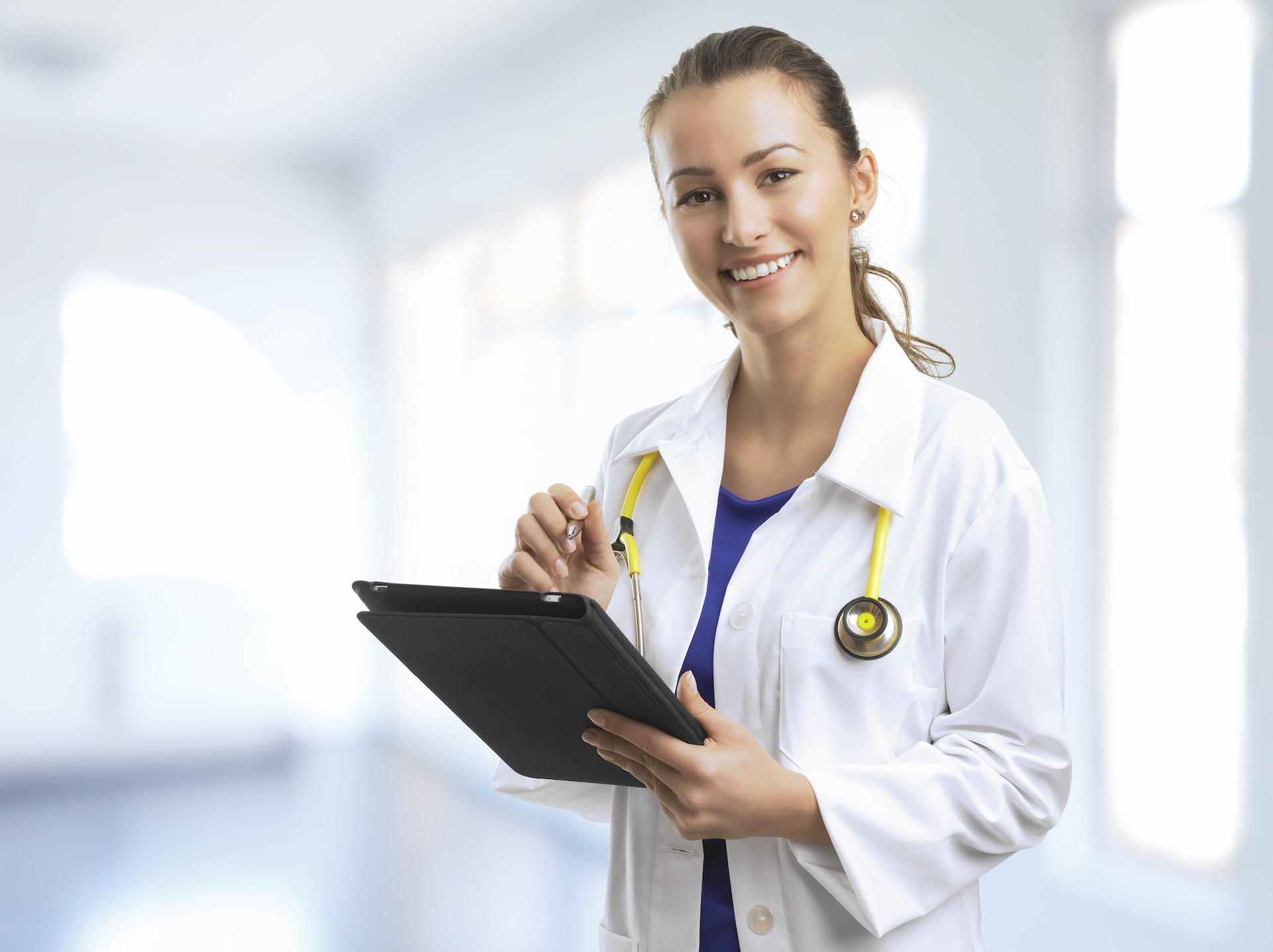 Female Doctor Standing At The Hospital With A Digital Tablet