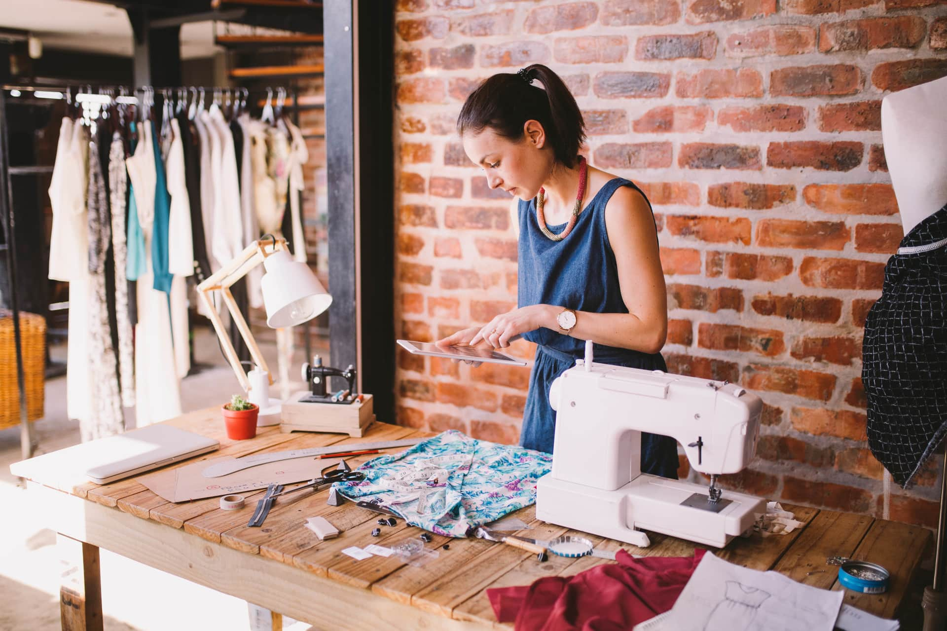 Fashion designer working with textiles in her boutique and ordering supplies on a digital tablet